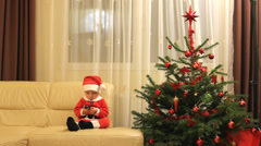 Adorable Santa Claus baby communicate to phone, Christmas fir tree Stock Footage