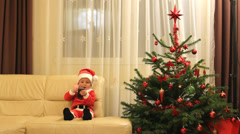 Happy Santa Claus baby with a phone near Christmas decorated fire tree Stock Footage