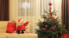 Lovely Santa Claus boy sit on couch near gift bag, Christmas ornaments, tree Stock Footage