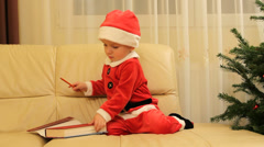 Little Santa Claus child open a book and try to write  - stock footage
