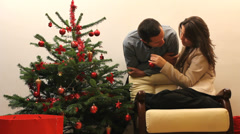 Young romantic couple stay near Christmas fir tree, lady arrange red ornament  - stock footage