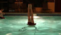Young man doing hand stand in indoor pool at night Stock Footage