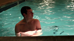 Young man standing in lighted pool and swims away Stock Footage