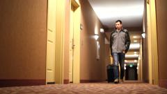 Young man pulling suitcase entering hotel room - stock footage