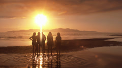 Group Of Five Girls Walking Out Onto A Sandbar At Sunset Stock Footage