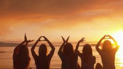 Group Of Five Girls Spell Out Love With Their Hands At Sunset On The Beach Stock Footage