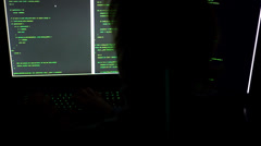 Hacker typing code on multiple screens Stock Footage