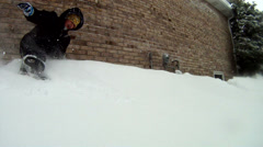 Young child knocking over deep snow drift Stock Footage
