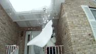 Stock Video Footage of Knocking down large snow drift on roof