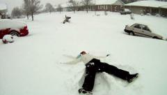 Teenaged girl making a snow angel Stock Footage