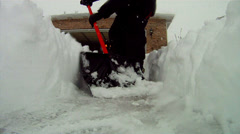 Super low angle of shoveling snow from driveway Stock Footage