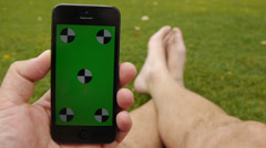 Using a smart phone at the park. Chroma Key Stock Footage