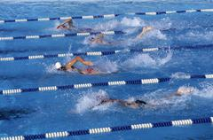 Swimmers competing in a race - stock photo