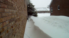 Snow drift along side of house with wind - stock footage