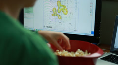 Working female snacking on popcorn in a home office Stock Footage