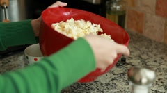 Woman adds salt and butter to popcorn Stock Footage