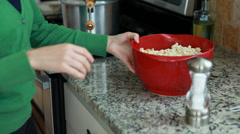 A lady adding salt and butter to popcorn Stock Footage