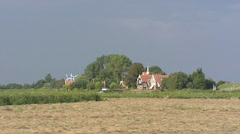 Picturesque dike houses along old sea dike in Dutch polder + zoom out hayland Stock Footage