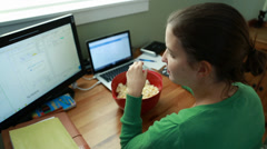 A woman snacking on popcorn in home office Stock Footage