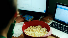 A woman snacking on popcorn while working at a home office Stock Footage