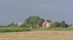 Hayland in Dutch polder landscape + zoom in wooden dike houses, old sea dike Stock Footage