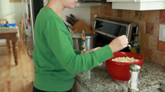 A woman adding salt and butter to popcorn Stock Footage