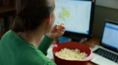 Working female snacking on popcorn while in a home office Stock Footage