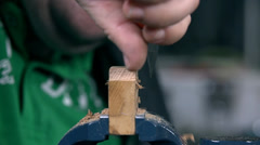 Cutting away useless parts of wooden chunk on a grip - stock footage