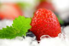strawberry with mint leaf on the ice cubes - stock photo