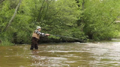 Trout fisherman casting a flyrod on a trout stream Stock Footage