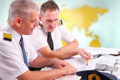 Stock Photo of airline pilots filling in papers in aro