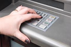 Woman's hand entering pin code on atm machine Stock Photos