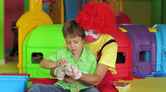 Birthday clown in full costume reading a book with kids - stock footage