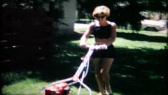 718 - the wife cuts the grass with the lawnmower - vintage film home movie - stock footage