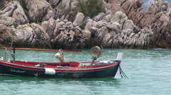 Swaying boat by a coastal rock in Montenegro Stock Footage