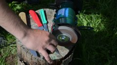 Hand sharpening knife with electric grinder  tool on wood log Stock Footage