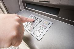 Finger pressing password number on atm machine Stock Photos