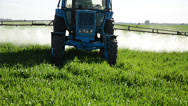 Stock Video Footage of Closeup tractor spray green field with pesticide chemicals