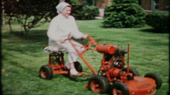 711 - mom cuts grass with the new riding lawnmower - vintage film home movie Stock Footage