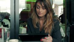Businesswoman reading an article on her tablet computer. In a cafe. Stock Footage