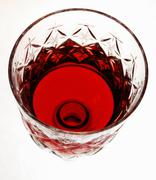 Footed tumbler of red wine over white Stock Photos