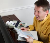 mature man goes into rage while work on his taxes - stock photo