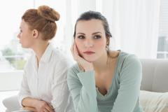 Unhappy friends not talking after argument on the couch Stock Photos