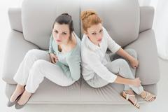 Unhappy young female friends not talking after argument on the couch - stock photo