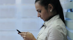 Closeup portrait of beautiful Indian businesswoman sending text message using mo - stock footage