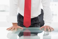 Mid section of a businessman with hands on desk - stock photo
