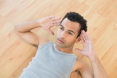 Stock Photo of Young man doing abdominal crunches on parquet floor