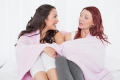 Female friends covered in sheet while chatting on bed Stock Photos