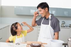 Girl and father holding cookie molds in kitchen Stock Photos