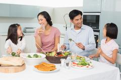 Young family of four enjoying healthy meal in kitchen Stock Photos